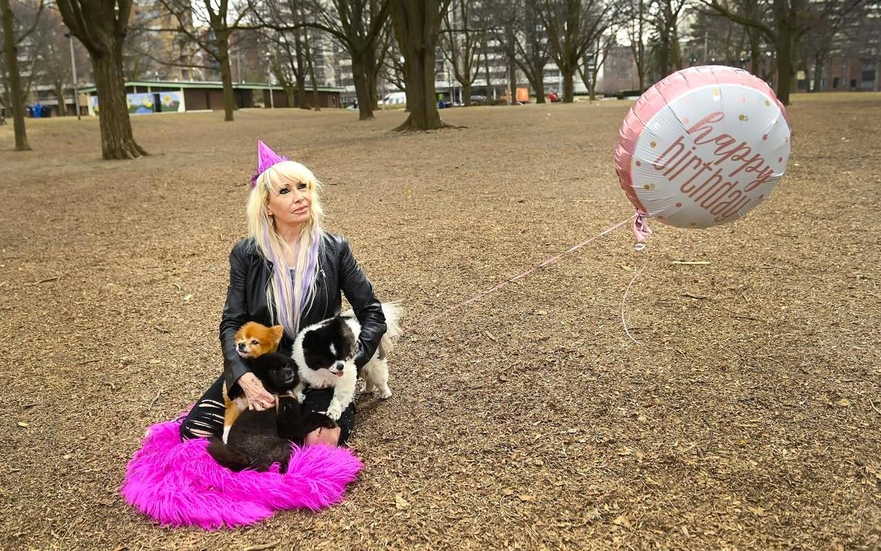 Eve Fischer, 57, sits alone in the park with her dogs after seeing her usual birthday gathering dashed for the second time due to the COVID-19 pandemic restrictions in Toronto on Tuesday, March 23, 2021. THE CANADIAN PRESS/Nathan Denette