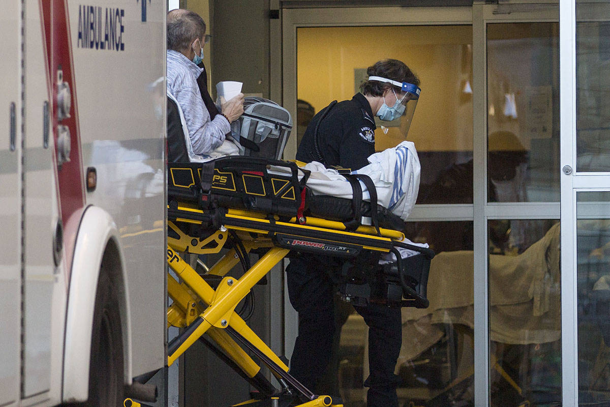 Medical personnel wear protective gear to wheel a patient into St. Paul's Hospital in Vancouver, B.C. on Wednesday, Dec. 2, 2020. B.C. THE CANADIAN PRESS/Marissa Tiel