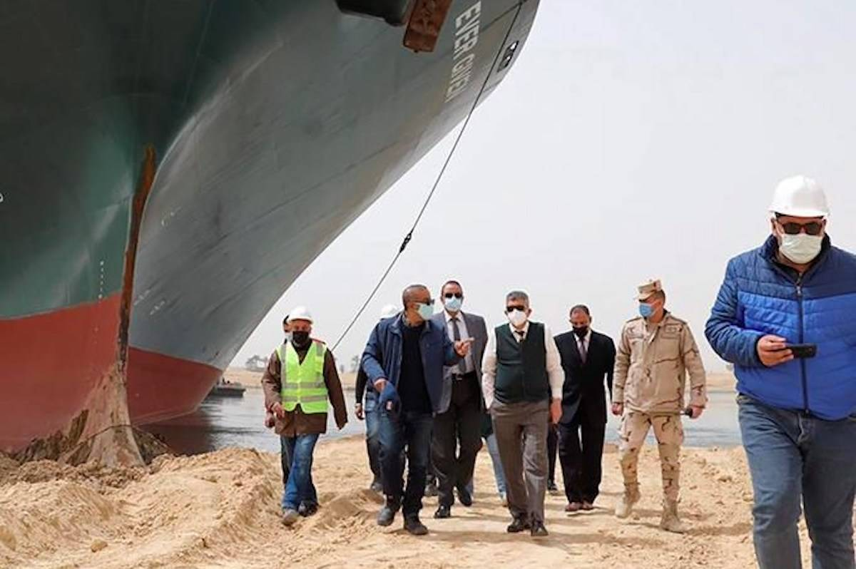 Lt. Gen. Ossama Rabei, center, head of the Suez Canal Authority, with a team walk along the bank of the Suez Canal where the Ever Given, a Panama-flagged cargo ship, has become wedged across the Suez Canal and blocking traffic in the vital waterway. (Suez Canal Authority via AP)