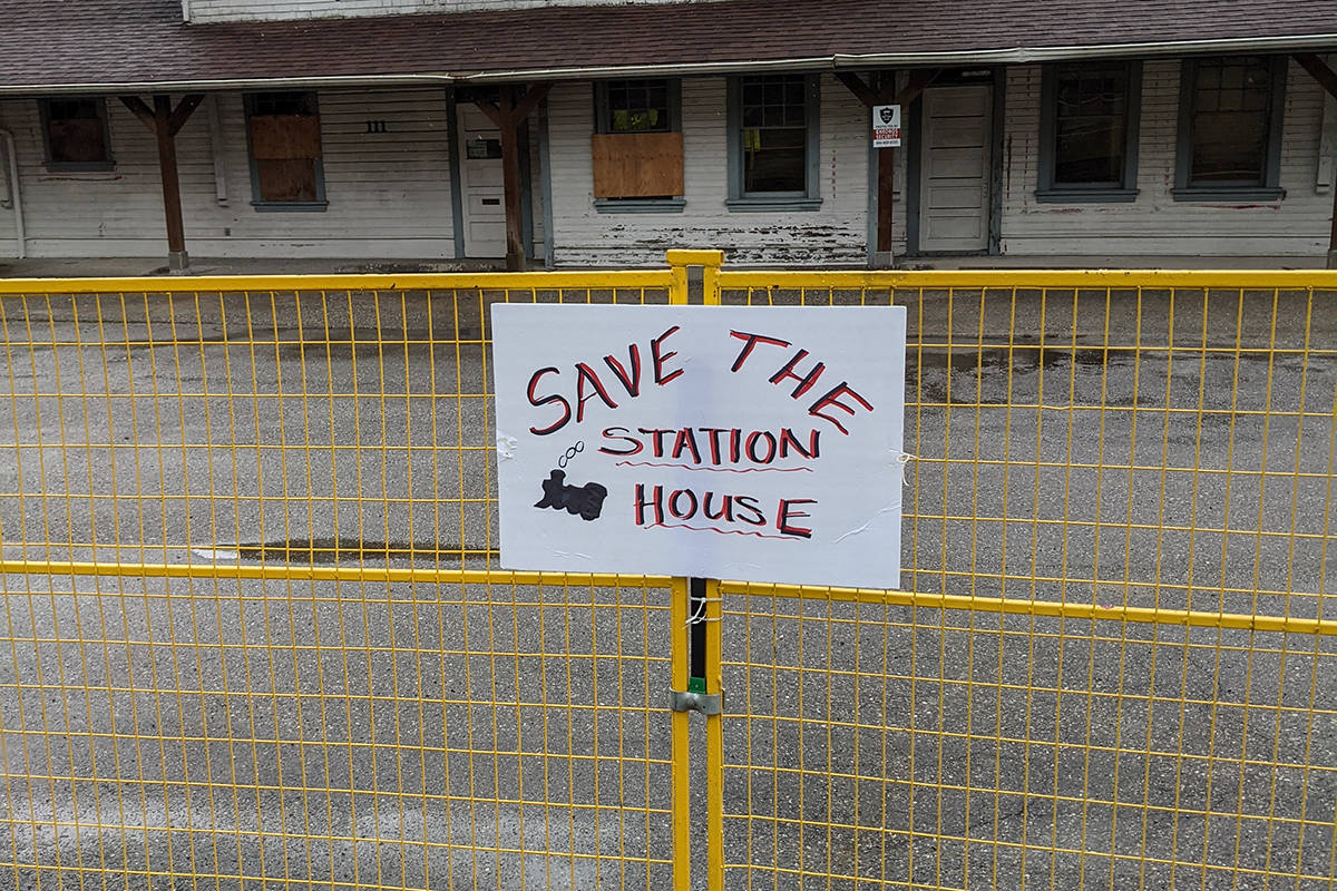 A few demonstrators from the weekend's walkathon left signs on the fence surrounding the Station House. (Photo/April Webster)