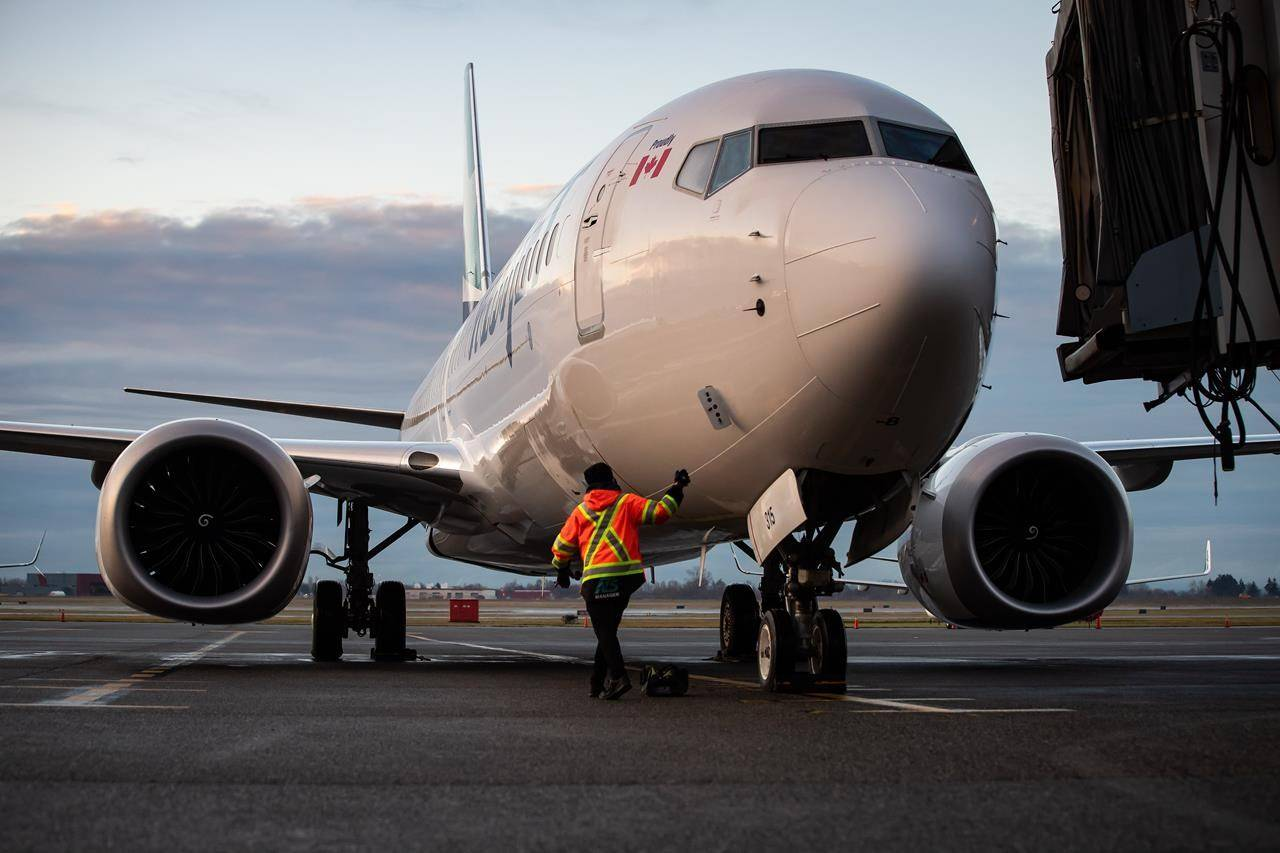 A ground worker approaches a WestJet Airlines Boeing 737 Max aircraft after it arrived at Vancouver International Airport in Richmond, B.C., on Thursday, January 21, 2021. THE CANADIAN PRESS/Darryl Dyck