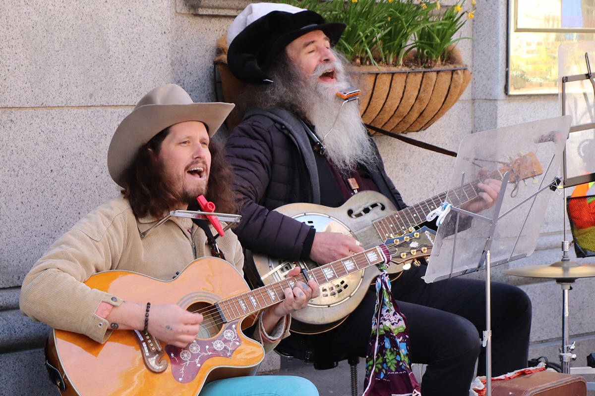 Frequent buskers Johnny Bomblast, left, and Dave Harris perform in front of Munro's Books on Government Street. The roommates recently completed a new album of original material entitled Clouds. (Don Descoteau/News Staff)