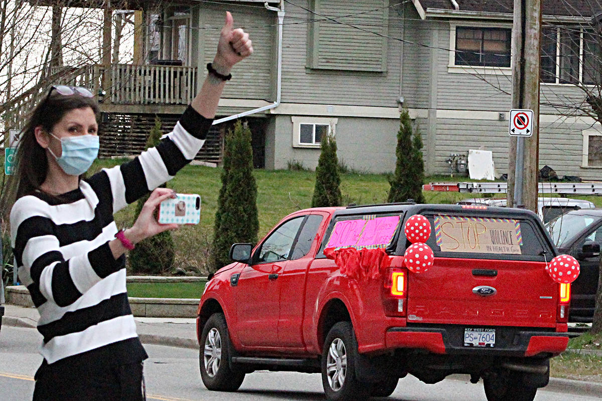 A supporter waves on the honking vehicles as they leave Mission Memorial Hospital. Patrick Penner / Mission Record.