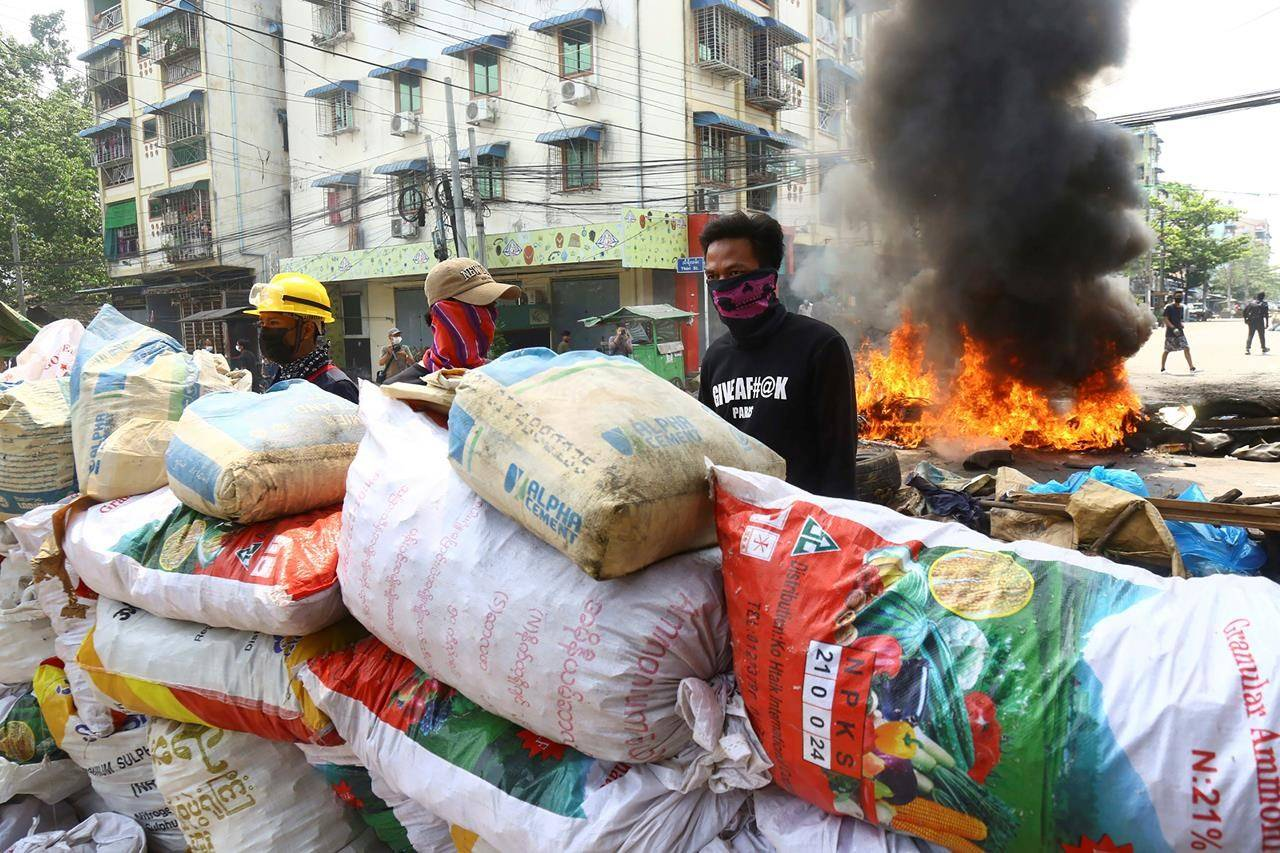Anti-coup protesters take positions behind their makeshift barricade in a protest in Yangon, Myanmar, Sunday, March 28, 2021. Protesters in Myanmar returned to the streets Sunday to press their demands for a return to democracy, just a day after security forces killed more than 100 people in the bloodiest day since last month's military coup. (AP Photo)