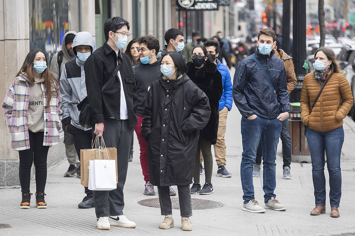 People wear face masks as they wait to cross a street in Montreal, Saturday, March 27, 2021, as the COVID-19 pandemic continues in Canada and around the world. THE CANADIAN PRESS/Graham Hughes