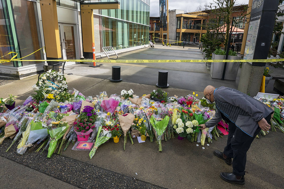 A man lays flowers at a makeshift memorial outside of the Lynn Valley Library in Lynn Valley in North Vancouver, B.C., Sunday, March 28, 2021. A 28-year-old man was charged Sunday with second-degree murder in a stabbing rampage that left a young woman dead and injured six others in and around a library in North Vancouver, B.C., a day earlier. THE CANADIAN PRESS/Jonathan Hayward