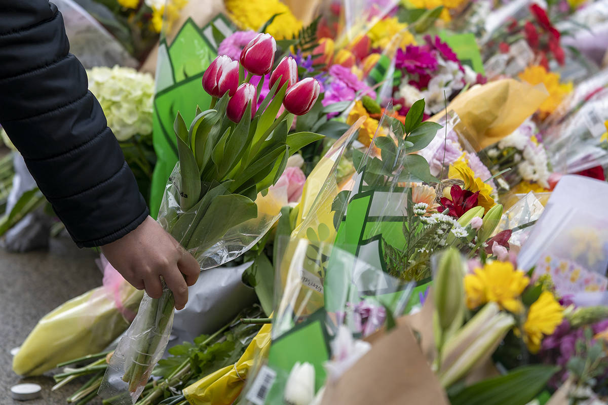 A person lays flowers at a makeshift memorial outside of the Lynn Valley Library in Lynn Valley in North Vancouver, B.C., Sunday, March 28, 2021. A 28-year-old man was charged Sunday with second-degree murder in a stabbing rampage that left a young woman dead and injured six others in and around a library in North Vancouver, B.C., a day earlier. THE CANADIAN PRESS/Jonathan Hayward