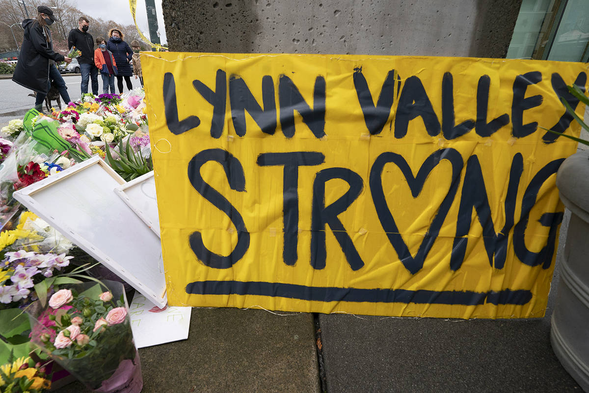 People lay flowers at a makeshift memorial outside of the Lynn Valley Library in Lynn Valley in North Vancouver, B.C., Sunday, March 28, 2021. A 28-year-old man was charged Sunday with second-degree murder in a stabbing rampage that left a young woman dead and injured six others in and around a library in North Vancouver, B.C., a day earlier. THE CANADIAN PRESS/Jonathan Hayward