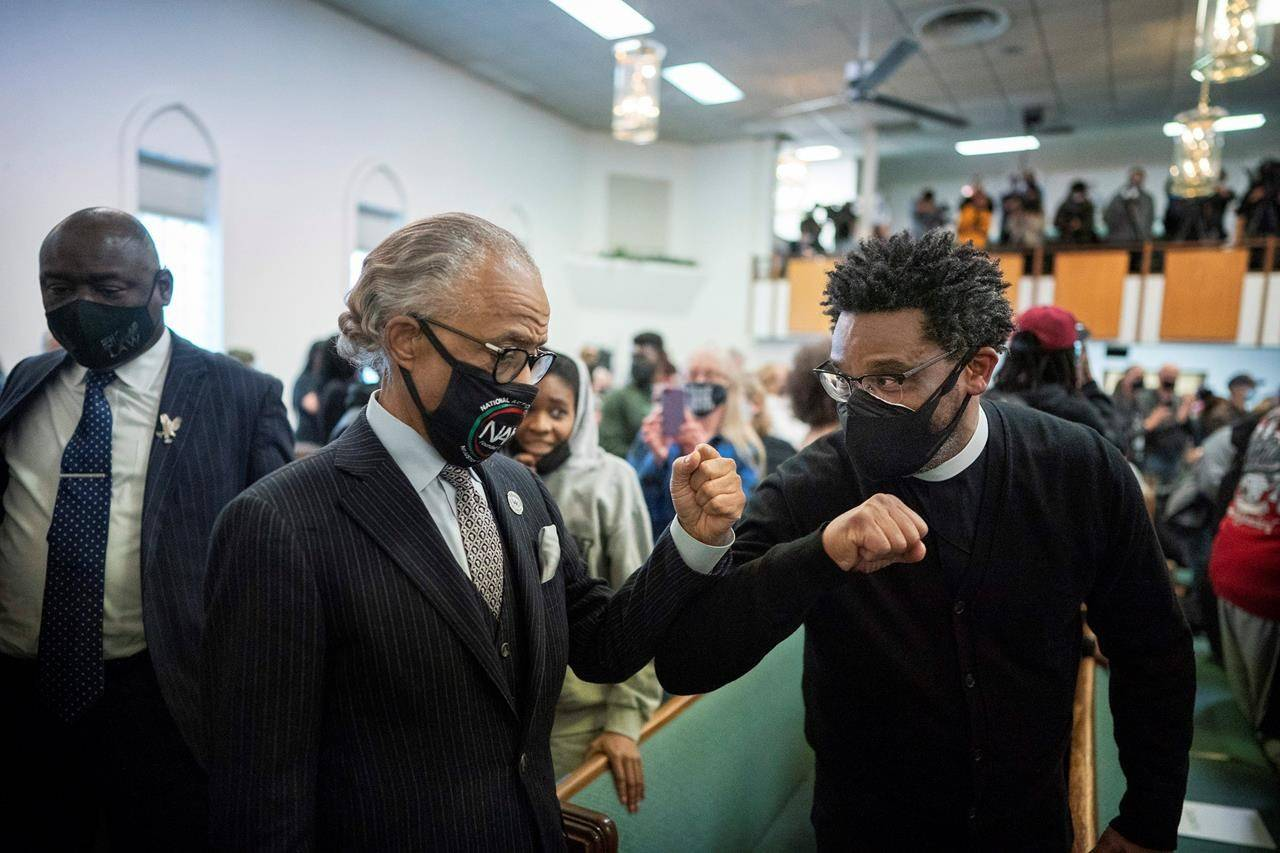 The Rev. Al Sharpton, left, elbow bumps a man as he arrived for a vigil for the family of George Floyd at Greater Friendship Church, Sunday, March 28, 2021, in Minneapolis. Opening statements are set for Monday in the trial of a former Minneapolis police officer charged with murder and manslaughter in George Floyd's death. (Jerry Holt/Star Tribune via AP)