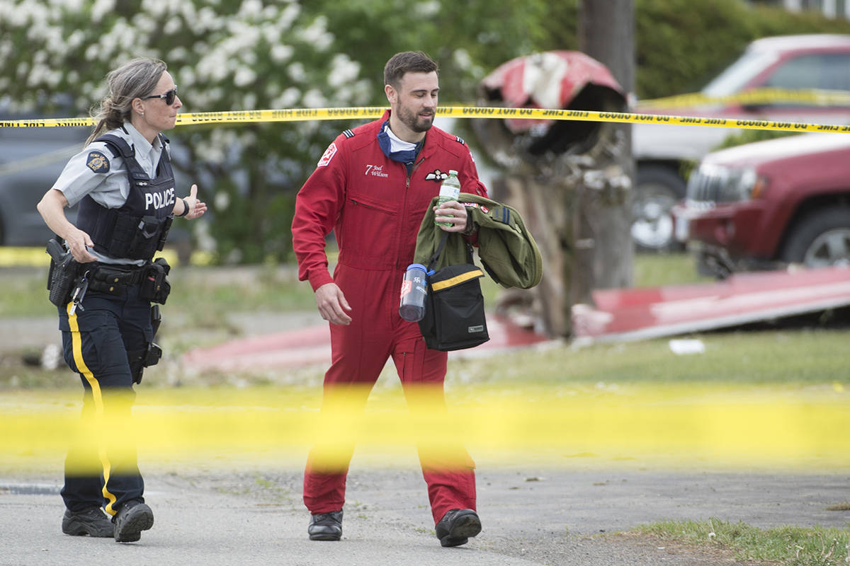 Canadian Forces Snowbird pilot Joel Wilson walks past the crash site of one of his team's plane in Kamloops, B.C., Sunday, May 17, 2020.  One person has died and another is badly injured after a Canadian Forces Snowbird plane crashed in a residential area of Kamloops, B.C., while on a cross-country tour meant to impart hope during the COVID-19 pandemic. THE CANADIAN PRESS/Jonathan Hayward