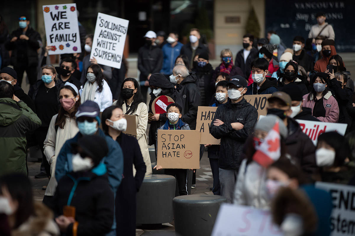 A young boy and others hold signs during a rally opposing discrimination against Asian communities and to mourn the victims of those affected by the Atlanta shootings, in Vancouver, B.C., on Sunday, March 28, 2021. THE CANADIAN PRESS/Darryl Dyck