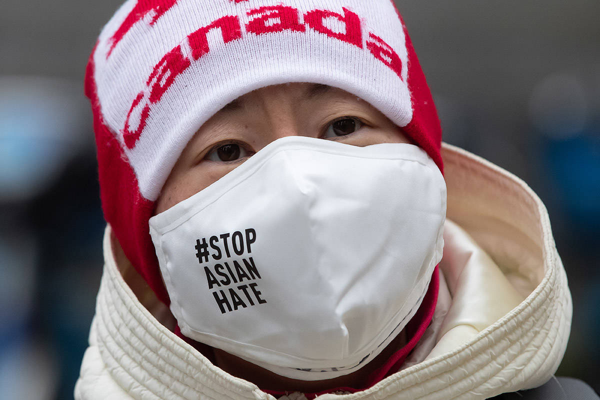 """A woman wears a face mask that says """"Stop Asian Hate"""" and a Canada toque during a rally opposing discrimination against Asian communities and to mourn the victims of those affected by the Atlanta shootings, in Vancouver, B.C., on Sunday, March 28, 2021. THE CANADIAN PRESS/Darryl Dyck"""