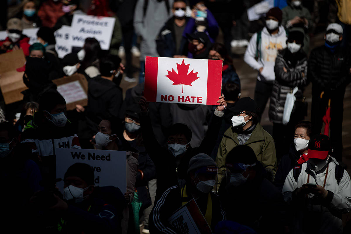 """A person holds a Canadian flag sign with the words """"No Hate"""" on it during a rally opposing discrimination against Asian communities and to mourn the victims of those affected by the Atlanta shootings, in Vancouver, B.C., on Sunday, March 28, 2021. THE CANADIAN PRESS/Darryl Dyck"""