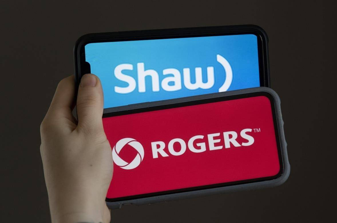 A woman holds two cellphones in this photo illustration, Monday March 29, 2021 in Chelsea, Que. The House of Commons Standing Committee on Industry, Science and Technology is hearing from Rogers and Shaw Communications executives on a merger. THE CANADIAN PRESS/Adrian Wyld
