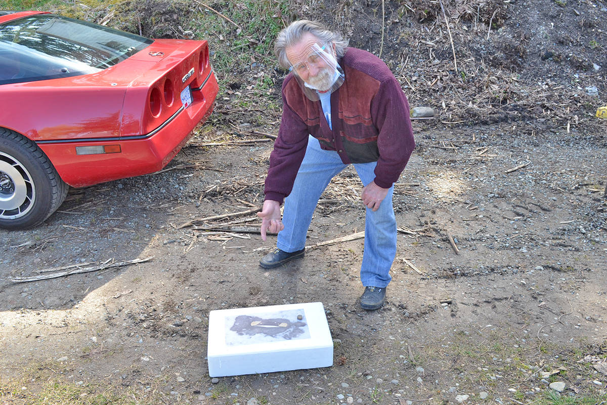 Ken Meuckon on March 26, 2021, next to a photo of the tracks he found on his property near Coombs Junction in the winter of 2019. (Mandy Moraes photo)
