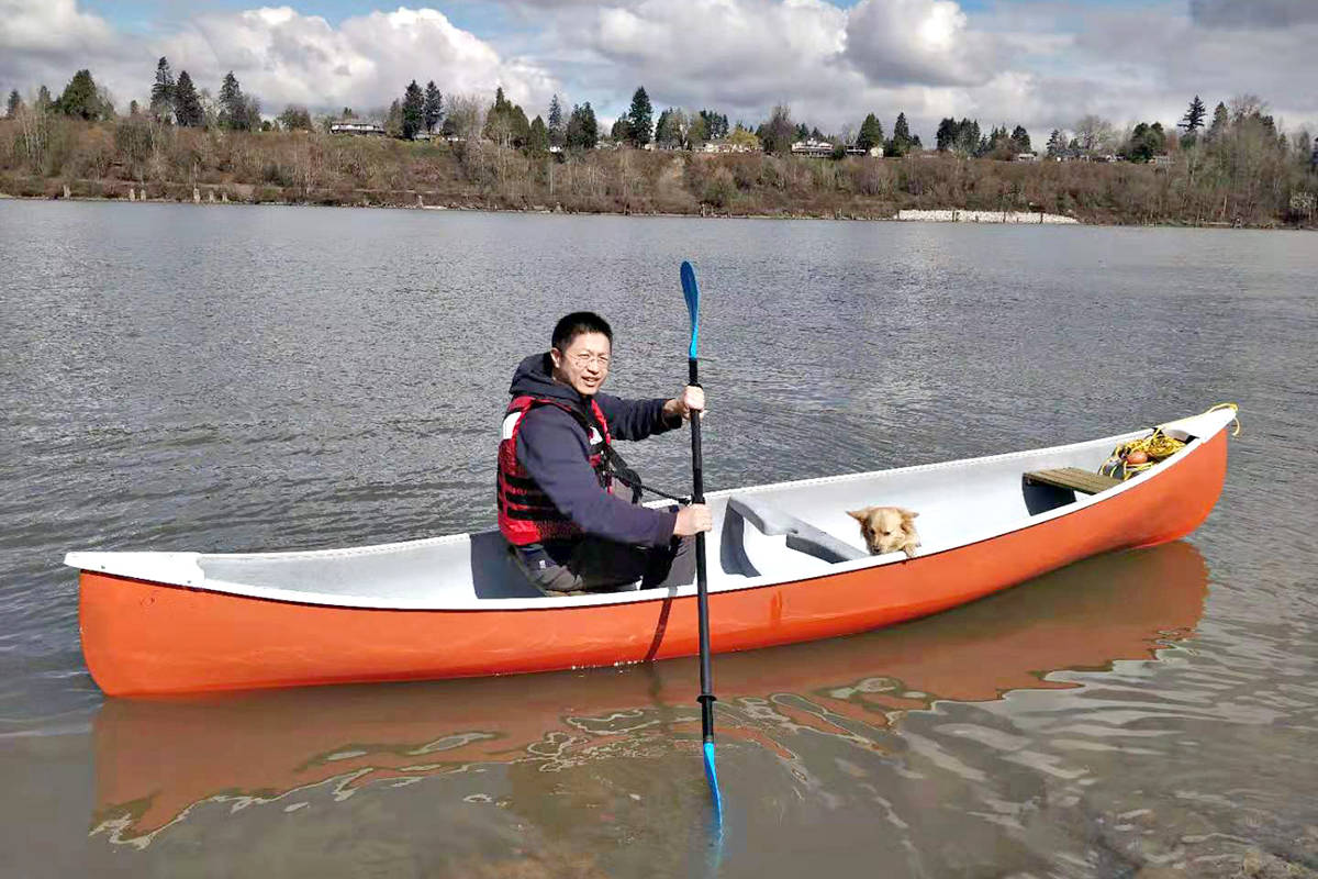 About 15 minutes after this photo was taken with his dog Chiu Chiu on the Fraser River near Derby Reach Park on Thursday, Langley Meadows resident Ruming Jiang ended up in the chilly water. (Special to Langley Advance Times)