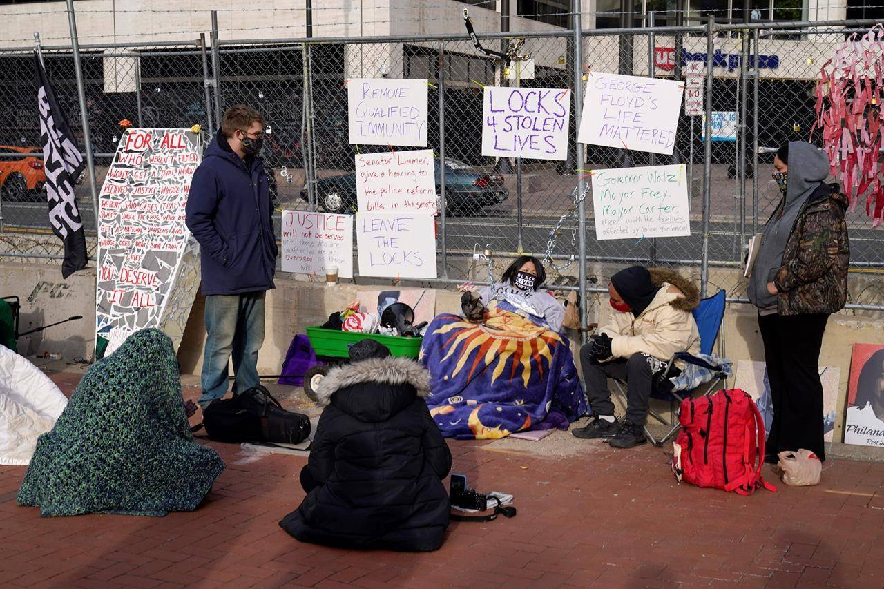 Protesters gather along a fence at the Hennepin County Government Center, Tuesday, March 30, 2021, in Minneapolis where the trial for former Minneapolis police officer Derek Chauvin continues. Chauvin is charged with murder in the death of George Floyd during an arrest last May in Minneapolis. (AP Photo/Jim Mone)