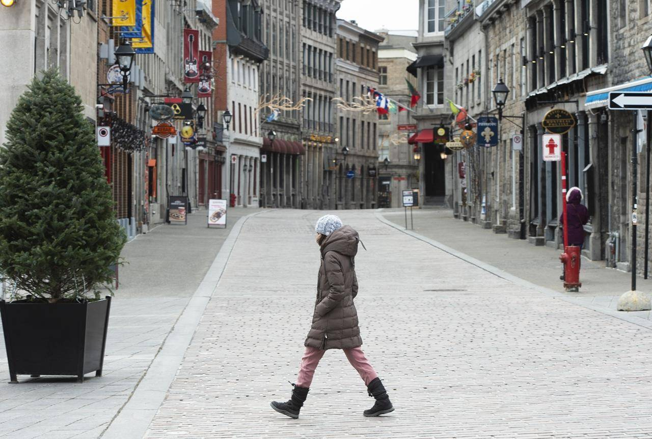 A pedestrian walks along a deserted street in Old Montreal, Wednesday, November 18, 2020 as the COVID-19 pandemic continues to impact tourism and the hospitality industry. Tourism spending in Canada dropped by 2 per cent in the fourth quarter of 2020, Statistics Canada says, capping off a disastrous year for the domestic tourism industry. THE CANADIAN PRESS/Ryan Remiorz