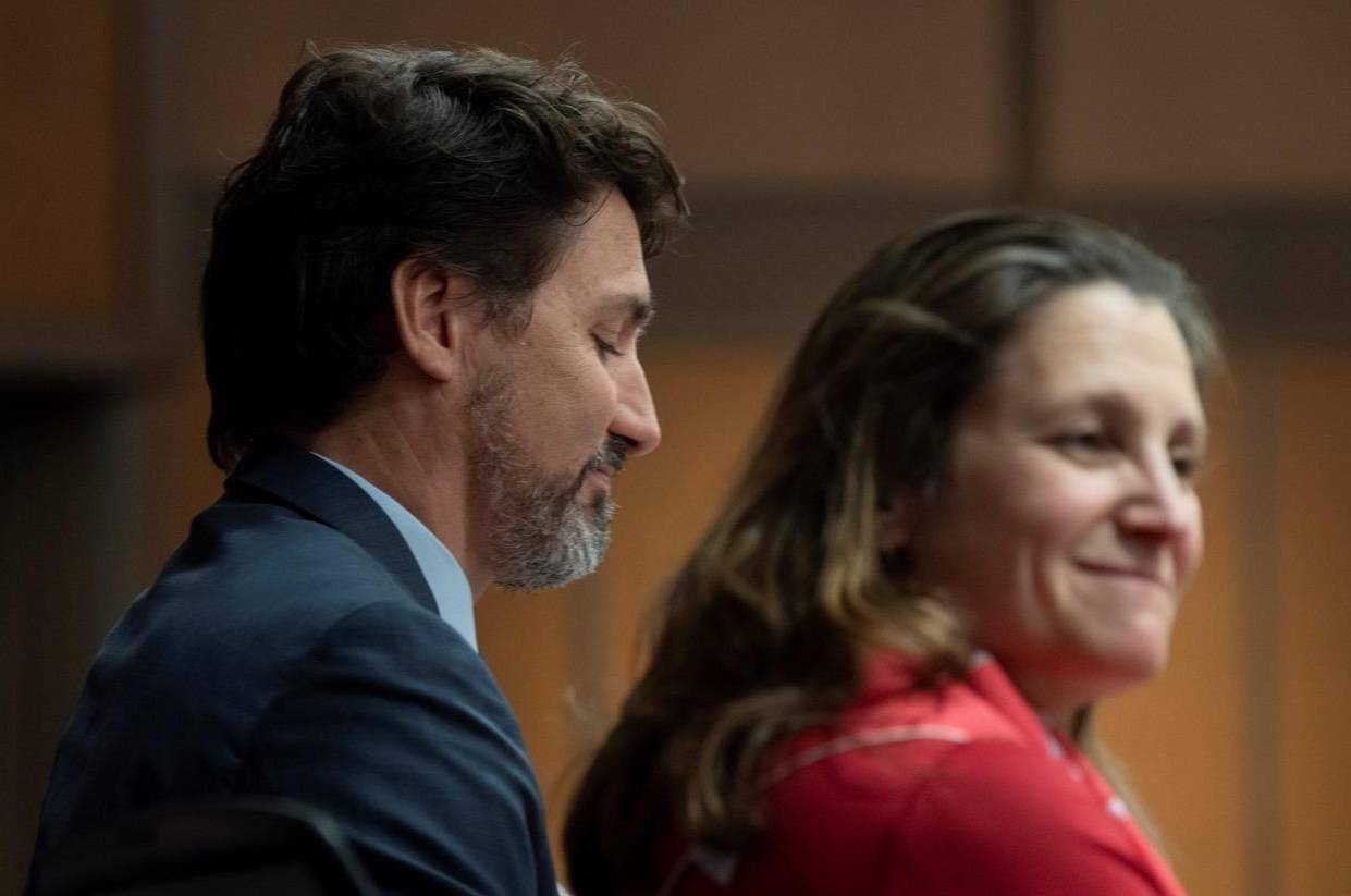 Prime Minister Justin Trudeau sits beside Deputy Prime Minister Chrystia Freeland before speaking to members of caucus on Parliament Hill in Ottawa, Thursday, January 23, 2020. Parliament's spending watchdog says the federal response to the COVID-19 pandemic should send the deficit to $363.4 billion. THE CANADIAN PRESS/Adrian Wyld