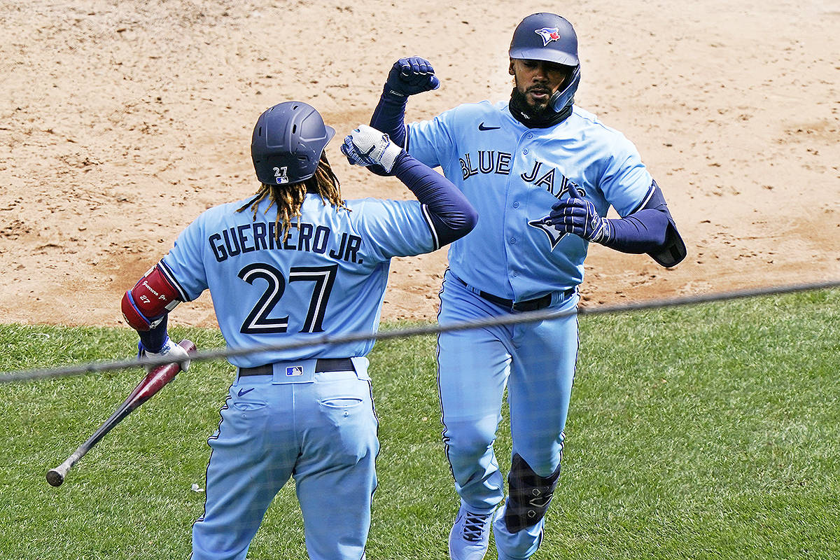 Toronto Blue Jays Vladimir Guerrero Jr. (27) celebrates with Blue Jays Teoscar Hernandez after Hernandez hit a game-tying solo home run off New York Yankees starting pitcher Gerrit Cole during the sixth inning of a major league baseball game on opening day at Yankee Stadium, Thursday, April 1, 2021, in New York. (AP Photo/Kathy Willens)