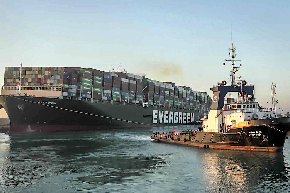 In this photo released by Suez Canal Authority, the Ever Given, a Panama-flagged cargo ship, is pulled by one of the Suez Canal tugboats, in the Suez Canal, Egypt, Monday, March 29, 2021. (Suez Canal Authority via AP)