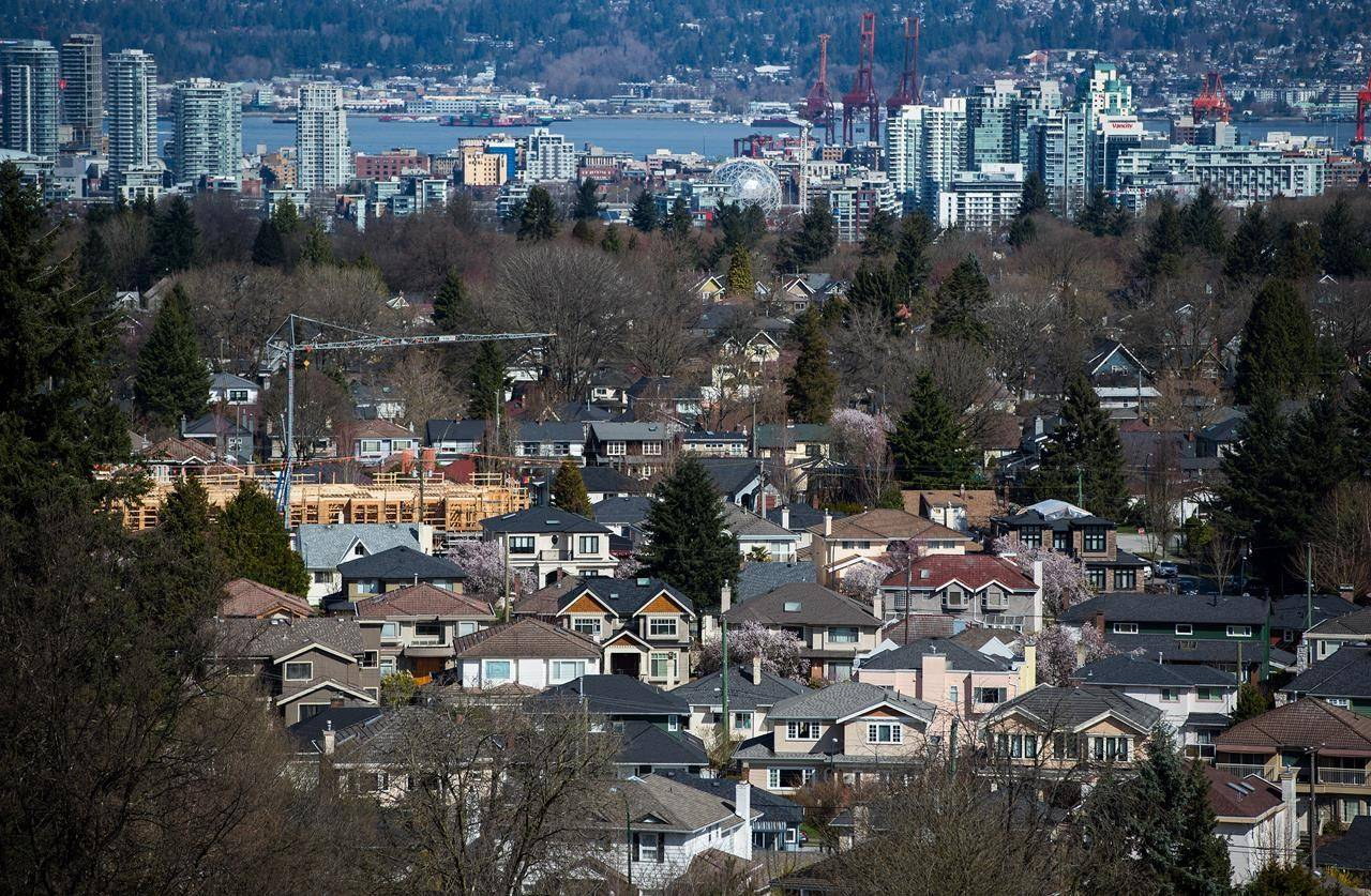 A condo building is seen under construction surrounded by houses as condo towers are seen in the distance in Vancouver, B.C., on Friday March 30, 2018. THE CANADIAN PRESS/Darryl Dyck