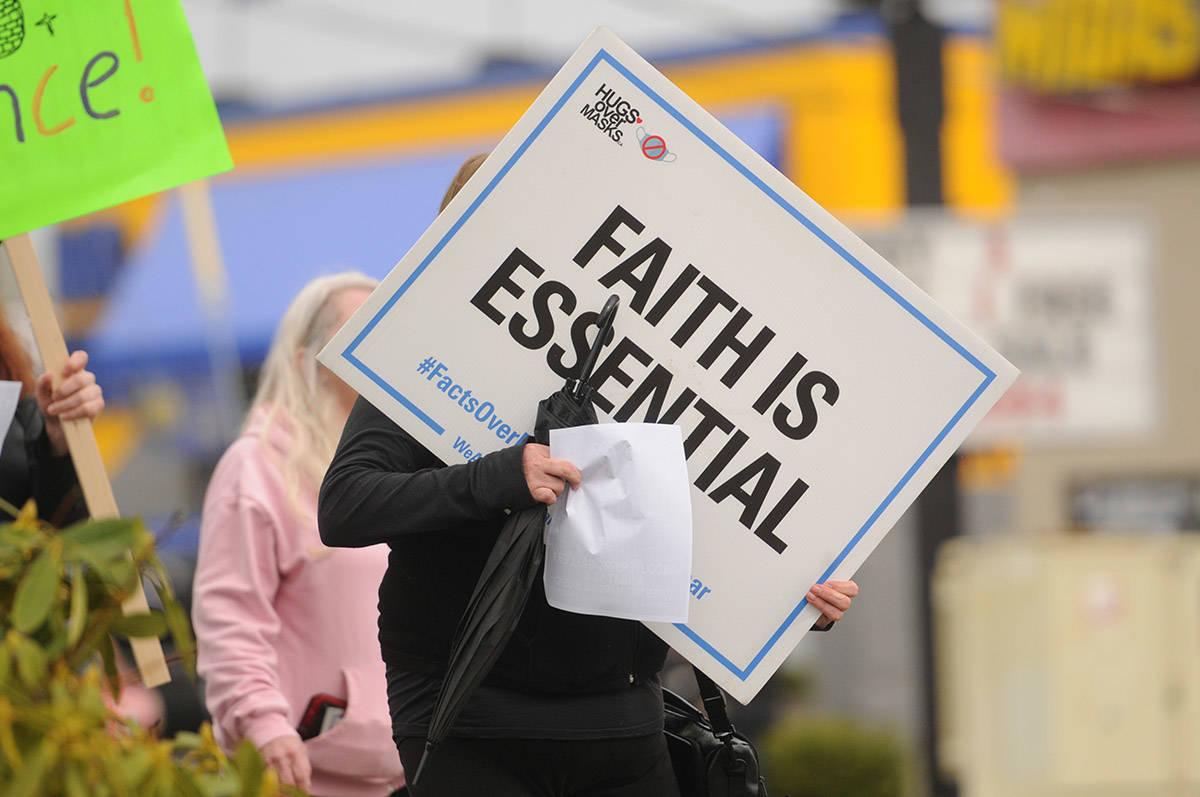 A protester holds a sign on Yale Road near Hodgins Avenue during the Fraser Valley Freedom Rally on Saturday, April 3, 2021. (Jenna Hauck/ Chilliwack Progress)