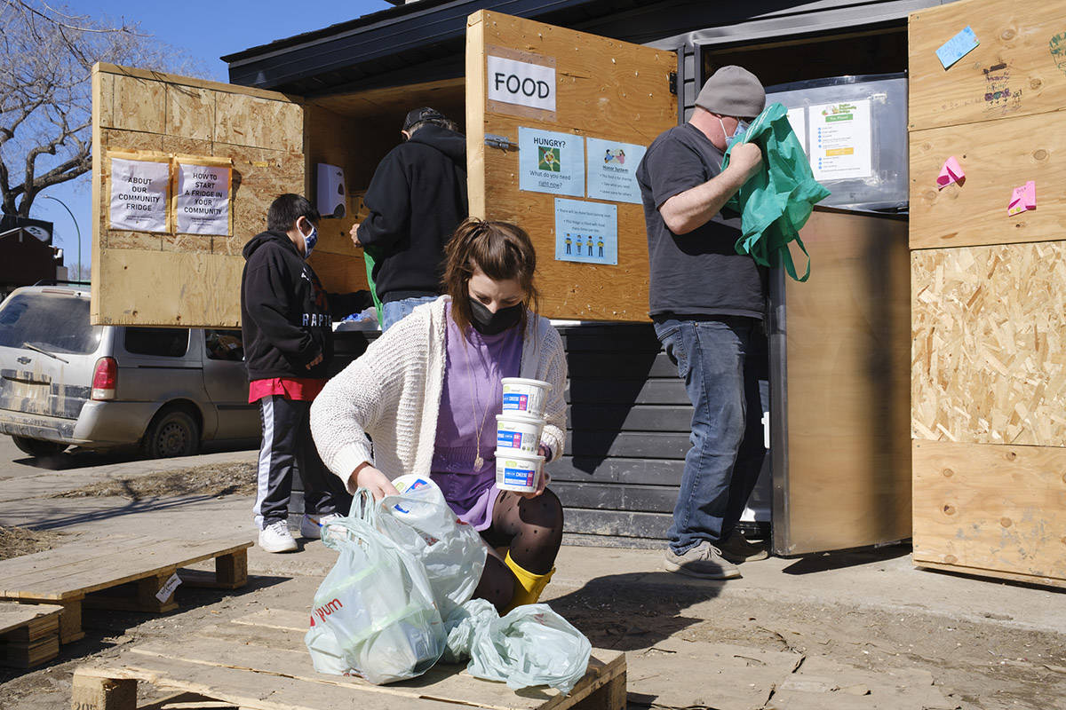 Danielle Froh, center, sorts out food donations for the Regina Community Fridge in Regina on Wednesday March 17, 2021. The community organization, of which Froh is a volunteer, exists to provide fresh food to anyone at anytime. THE CANADIAN PRESS/Michael Bell