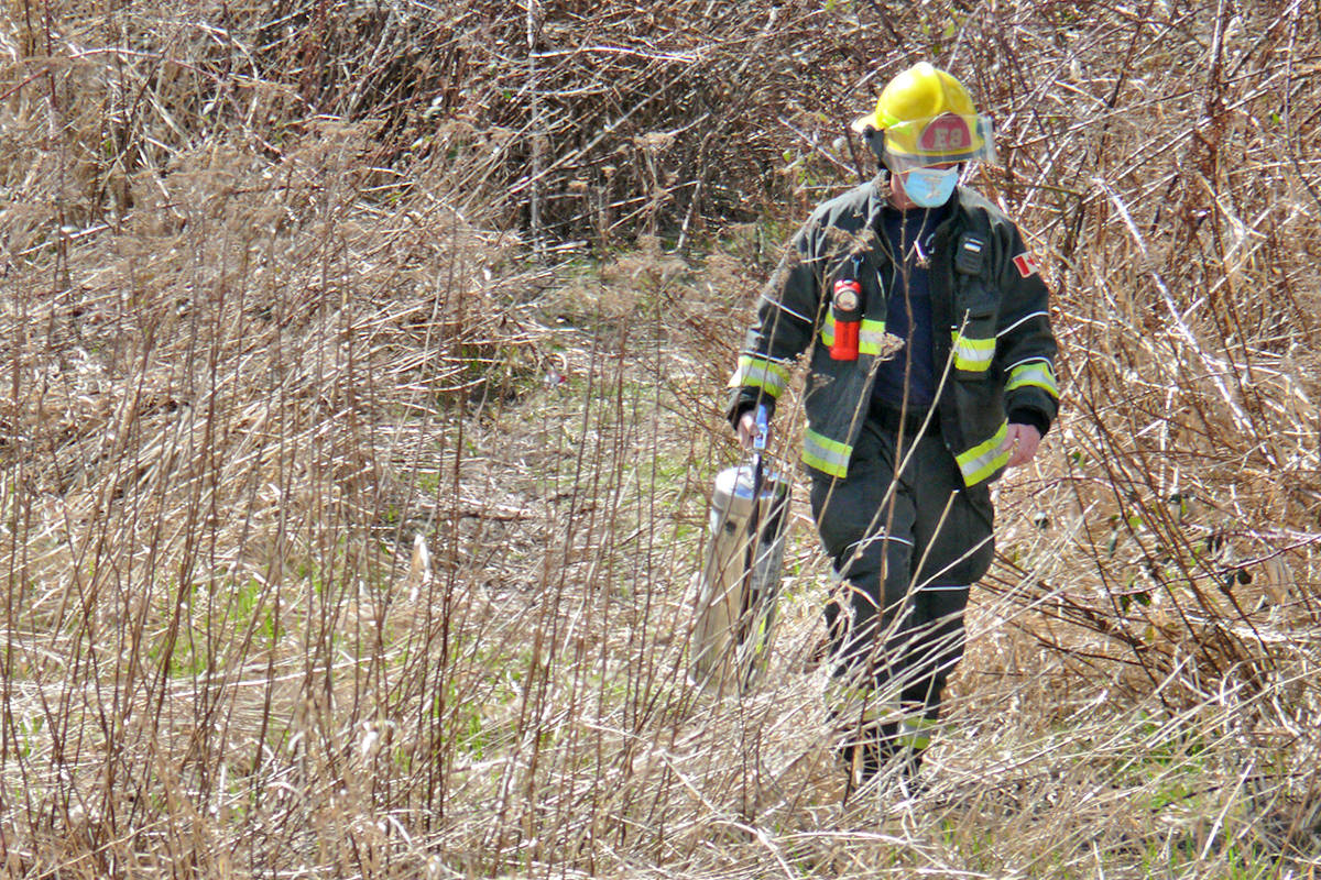 Fire crews lugged extinguishers into the deep brush at the west side of the Langley airport to fight a small fire on Sunday, April 4 (Dan Ferguson/Langley Advance Times)