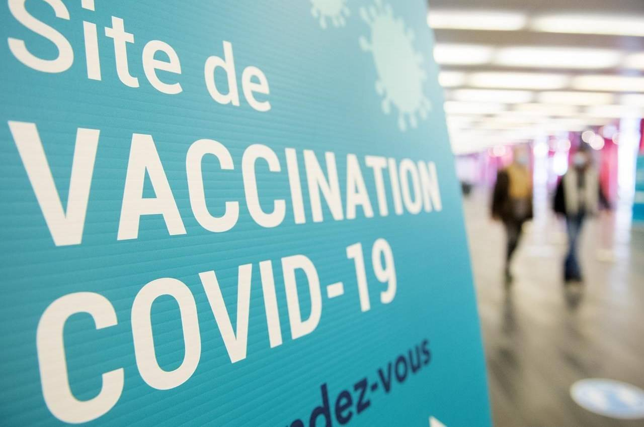 People walk by a sign for a COVID-19 vaccination site in Montreal, Sunday, April 4, 2021. THE CANADIAN PRESS/Graham Hughes