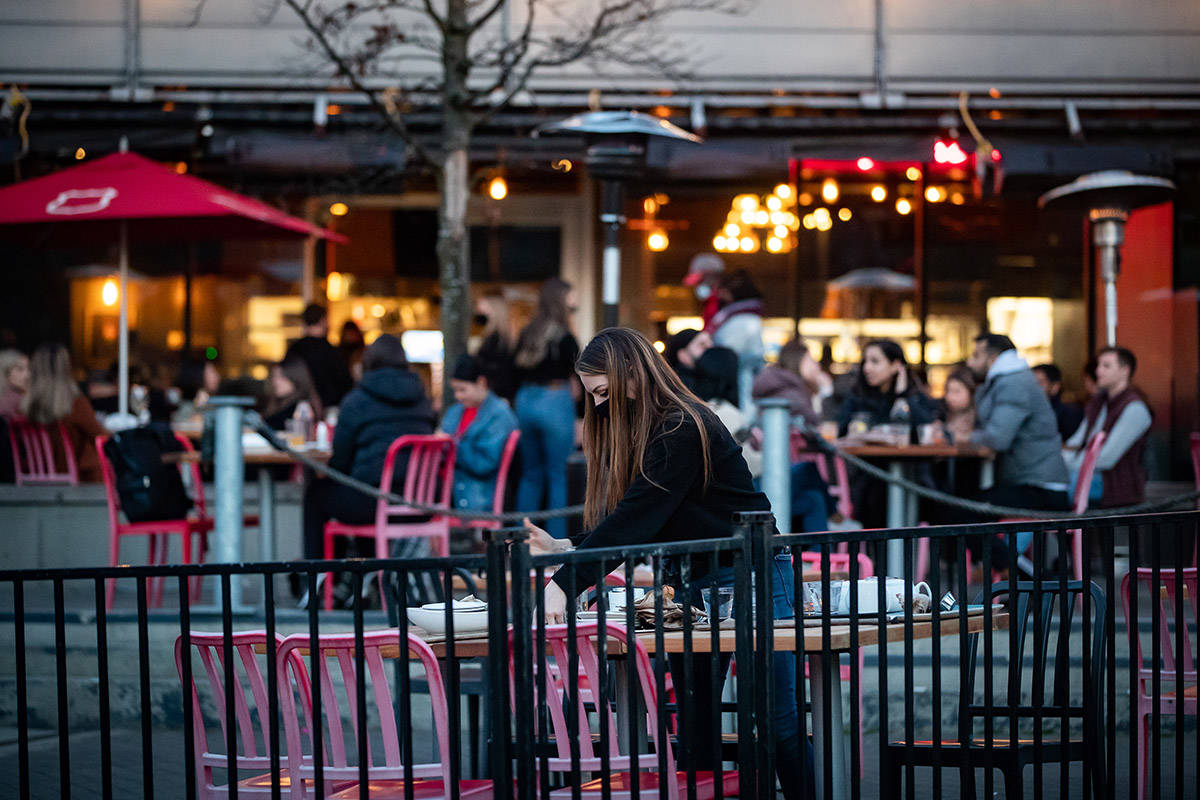 A server clears a table on a patio at a restaurant, in Vancouver, on Friday, April 2, 2021. B.C. has banned indoor dining at restaurants and bars as part of a three-week measure to curb the spread of COVID-19 amid growing concern about the spread of COVID-19 variants. THE CANADIAN PRESS/Darryl Dyck