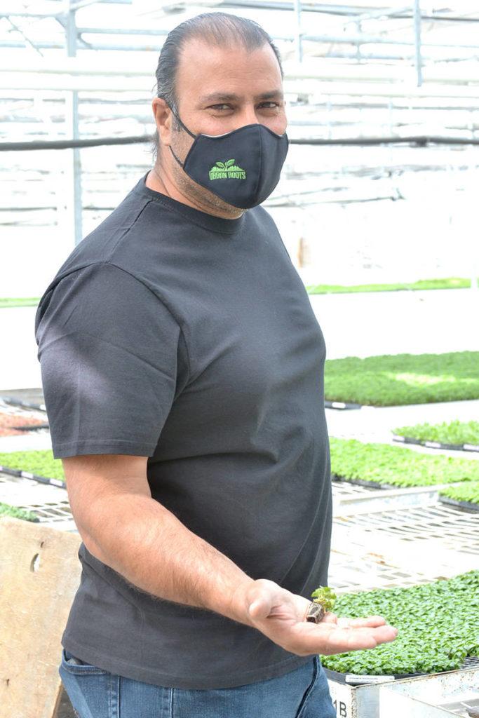 Bill Brar, co-owner of Canadian Valley Growers in Aldergrove, holds a sprouting Impatiens flower. (Ryan Uytdewilligen/Aldergrove Star)