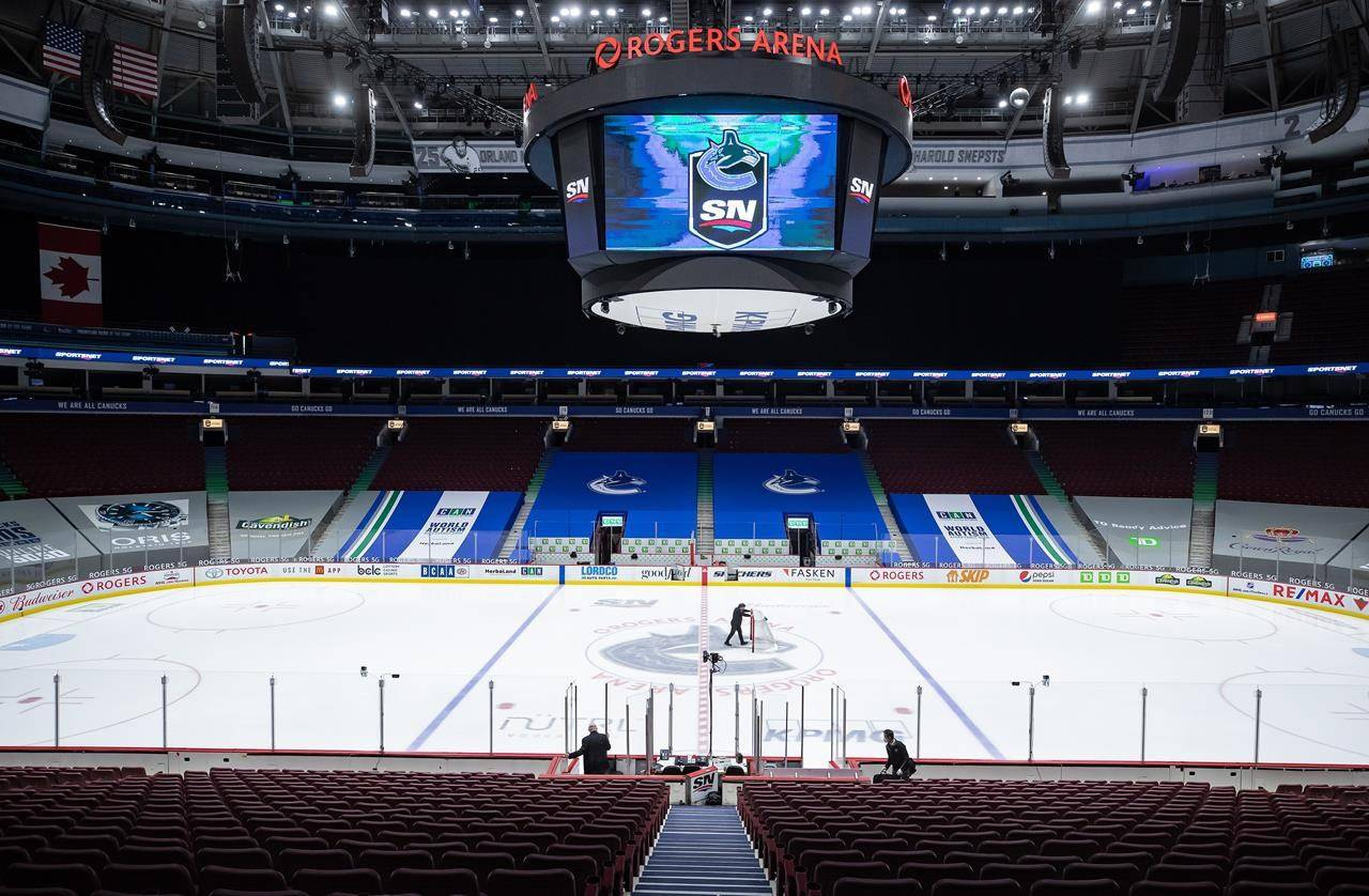 An arena worker removes the net from the ice after the Vancouver Canucks and Calgary Flames NHL hockey game was postponed due to a positive COVID-19 test result, in Vancouver, on Wednesday, March 31, 2021. THE CANADIAN PRESS/Darryl Dyck