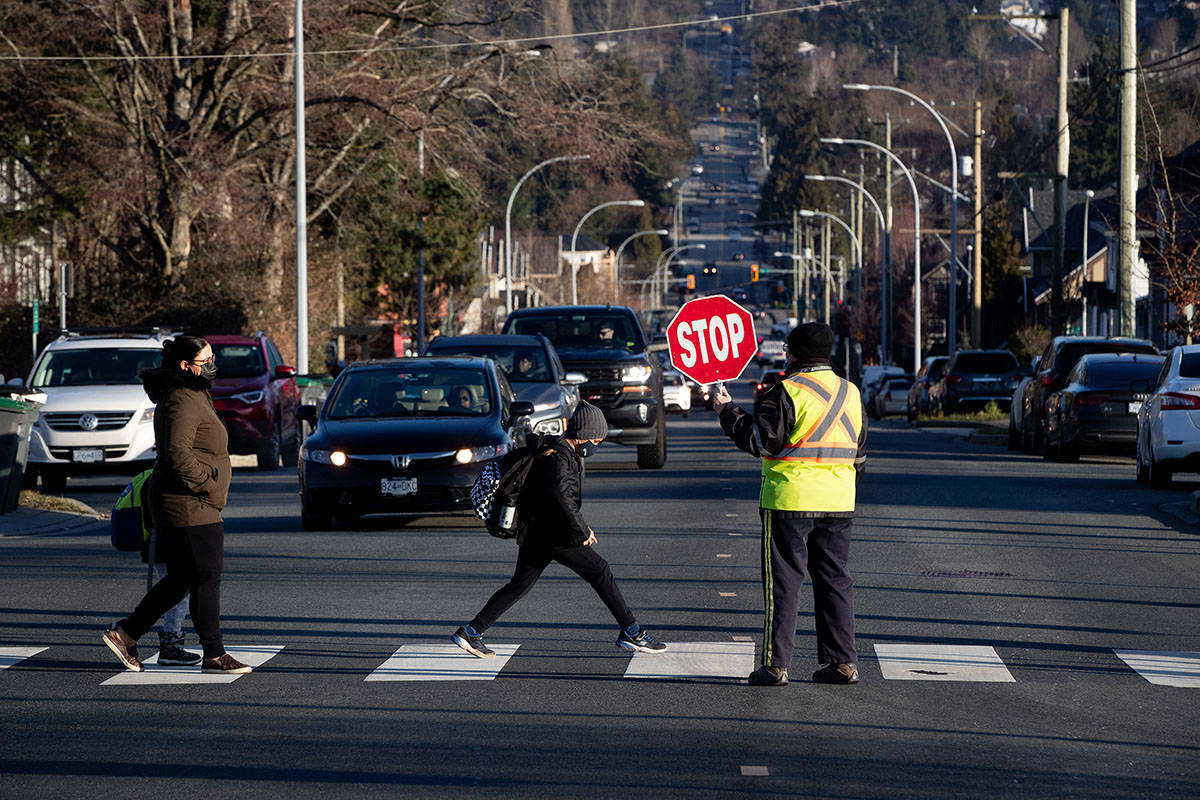 FILE – A crossing guard stops traffic as a student wearing a face mask to curb the spread of COVID-19 arrives at Ecole Woodward Hill Elementary School, in Surrey, B.C., on Tuesday, February 23, 2021. THE CANADIAN PRESS/Darryl Dyck