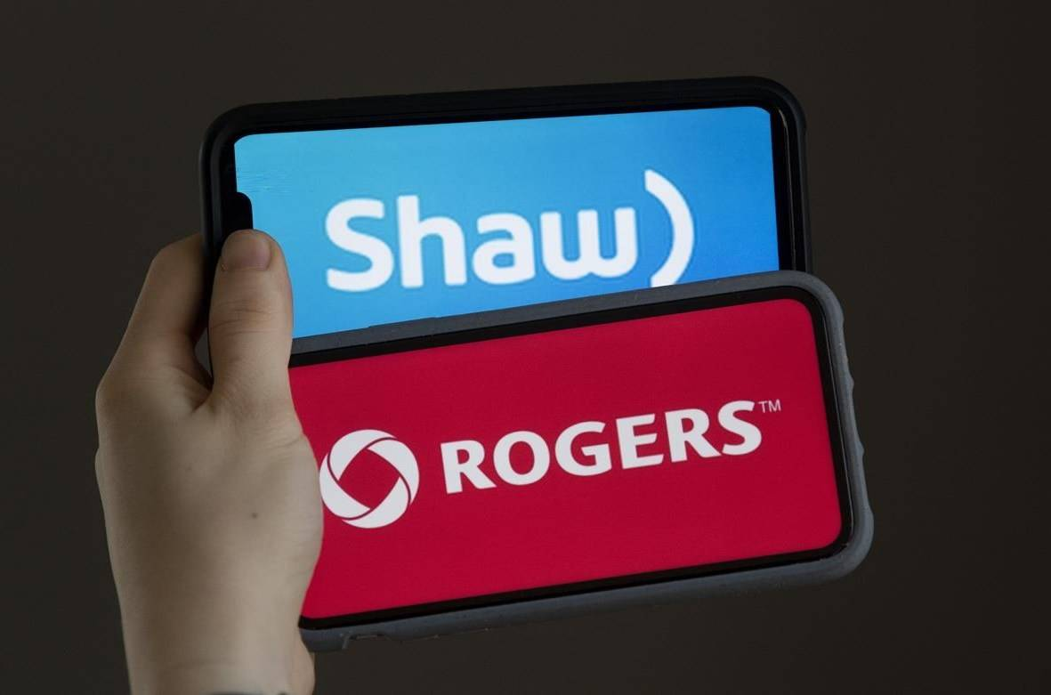 A woman holds two cellphones with the corporate logos of Rogers Communications and Shaw Communications in a photo illustration in Chelsea, Que., Monday March 29, 2021. A review of the proposed $26-billion purchase of Shaw Communications by Rogers Communications continues into its third day today in Ottawa before a committee of federal MPs. THE CANADIAN PRESS/Adrian Wyld