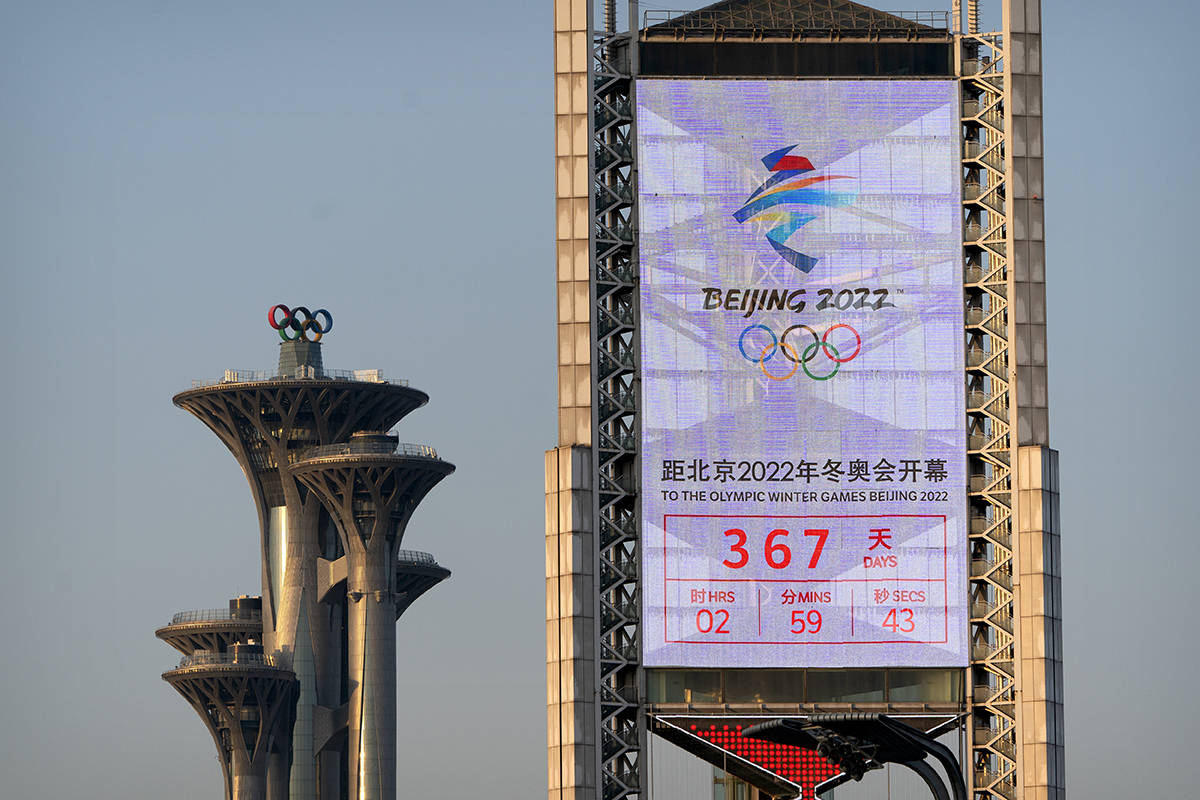 A screen displays a countdown clock showing slightly more than 1 year to go for the 2022 Beijing Olympics on a building near the Olympic Tower in Beijing, Tuesday, Feb. 2, 2021. A coalition of 180 rights group on Wednesday called for a boycott of next year's Beijing Winter Olympics tied to reported human rights abuses against ethnic minorities in China. (AP Photo/Mark Schiefelbein)