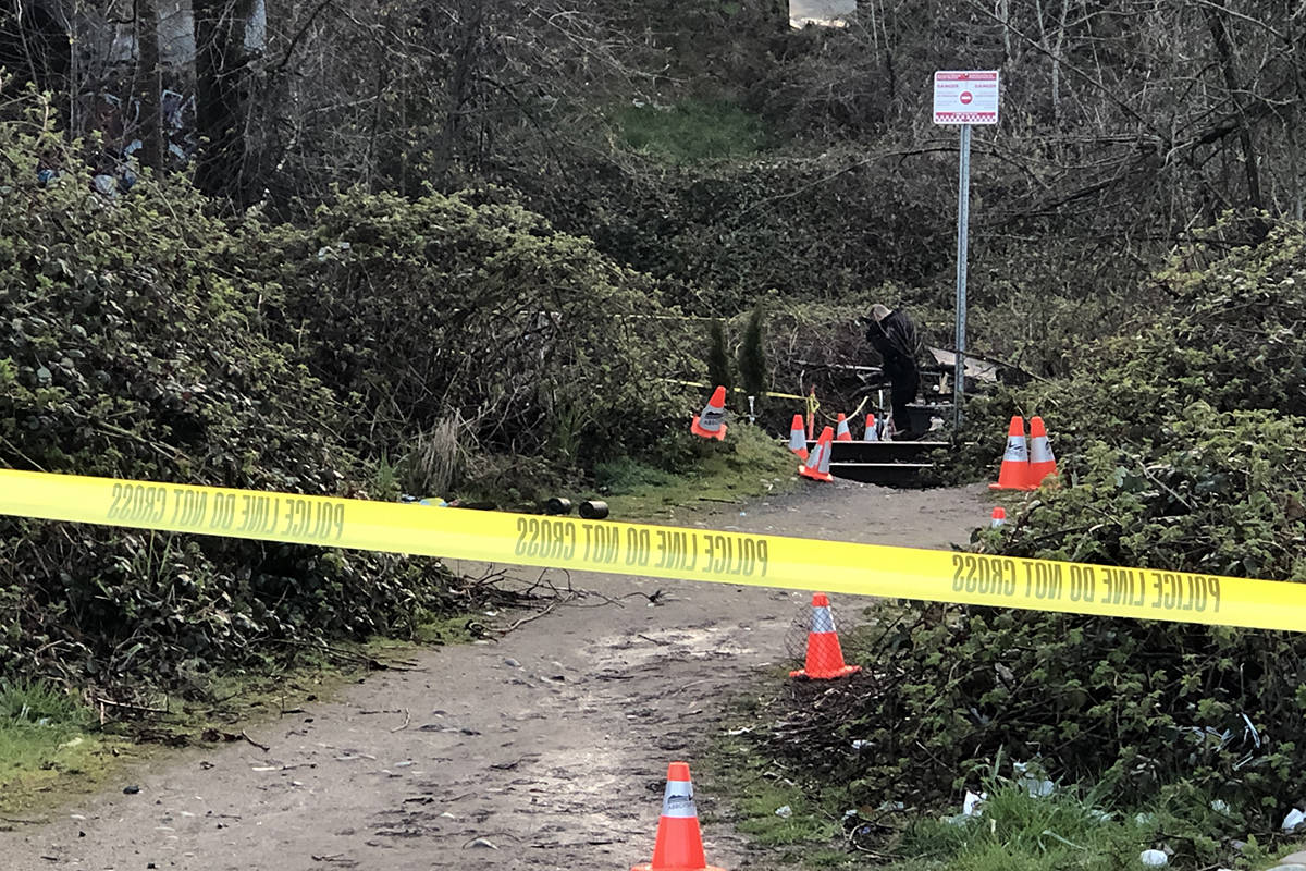 A large area of the railway tracks beneath a bridge on Highway 1 has been cordoned off by police tape as investigators collect evidence. Patrick Penner / Abbotsford News.