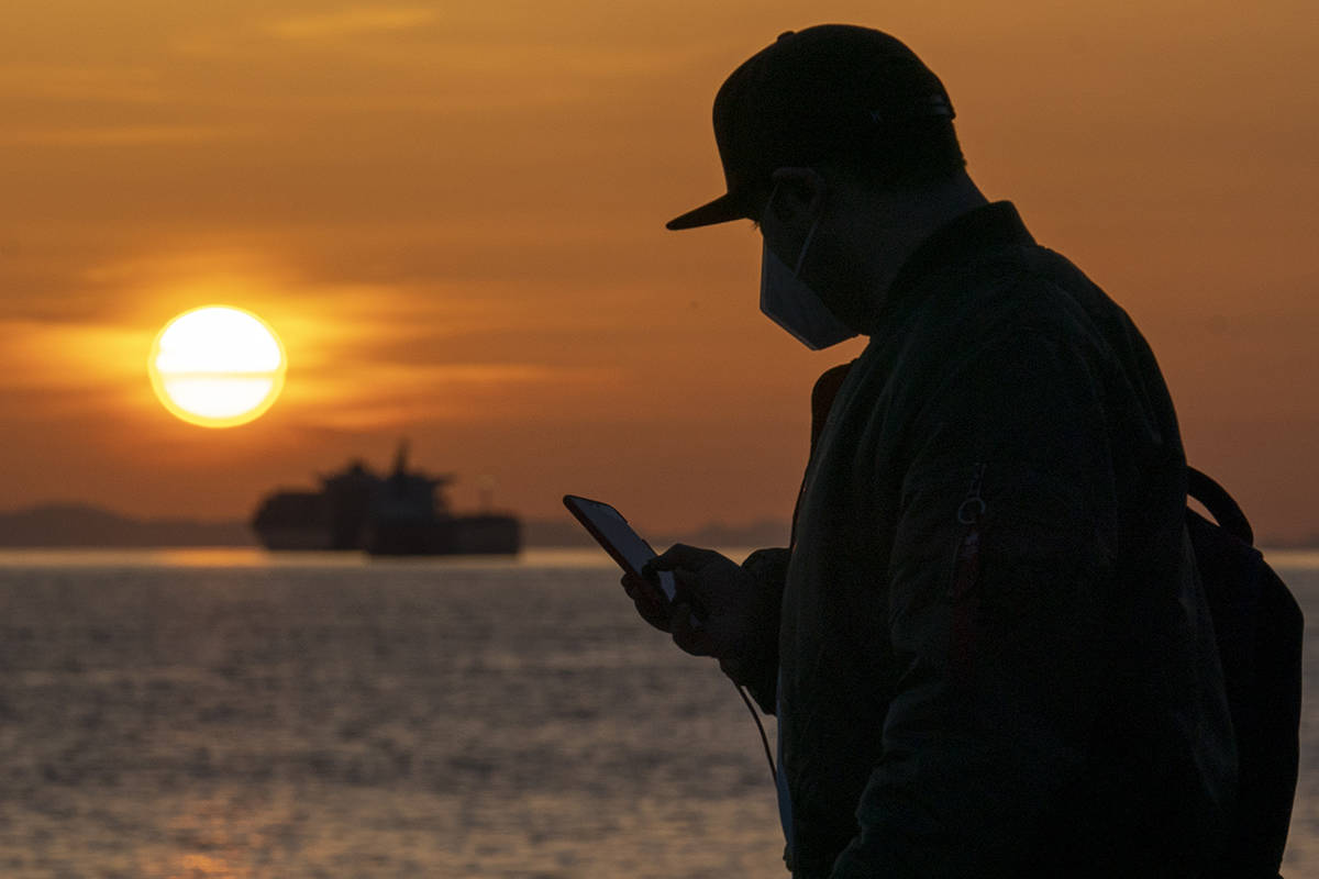 A man wearing a protective face mask to help prevent the spread of COVID-19 checks his phone as the sun sets in English Bay in Vancouver, B.C., Monday, April 5, 2021. THE CANADIAN PRESS/Jonathan Hayward