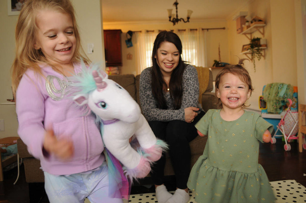 Two-year-old Ivy McLeod (right), seen here on April 9, 2021 with four-year-old sister Elena and mom Vanessa, was born with limb differences. The family, including husband/dad Sean McLeod, is looking for a family puppy that also has a limb difference. (Jenna Hauck/ Chilliwack Progress)