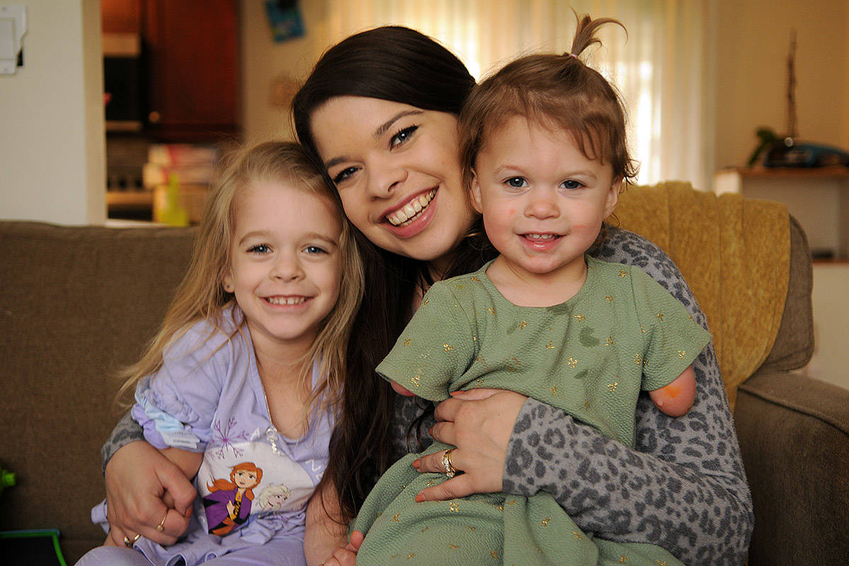 Two-year-old Ivy McLeod, seen here on April 9, 2021 with four-year-old sister Elena and mom Vanessa, was born with limb differences. The family, including husband/dad Sean McLeod, is looking for a family puppy that also has a limb difference. (Jenna Hauck/ Chilliwack Progress)