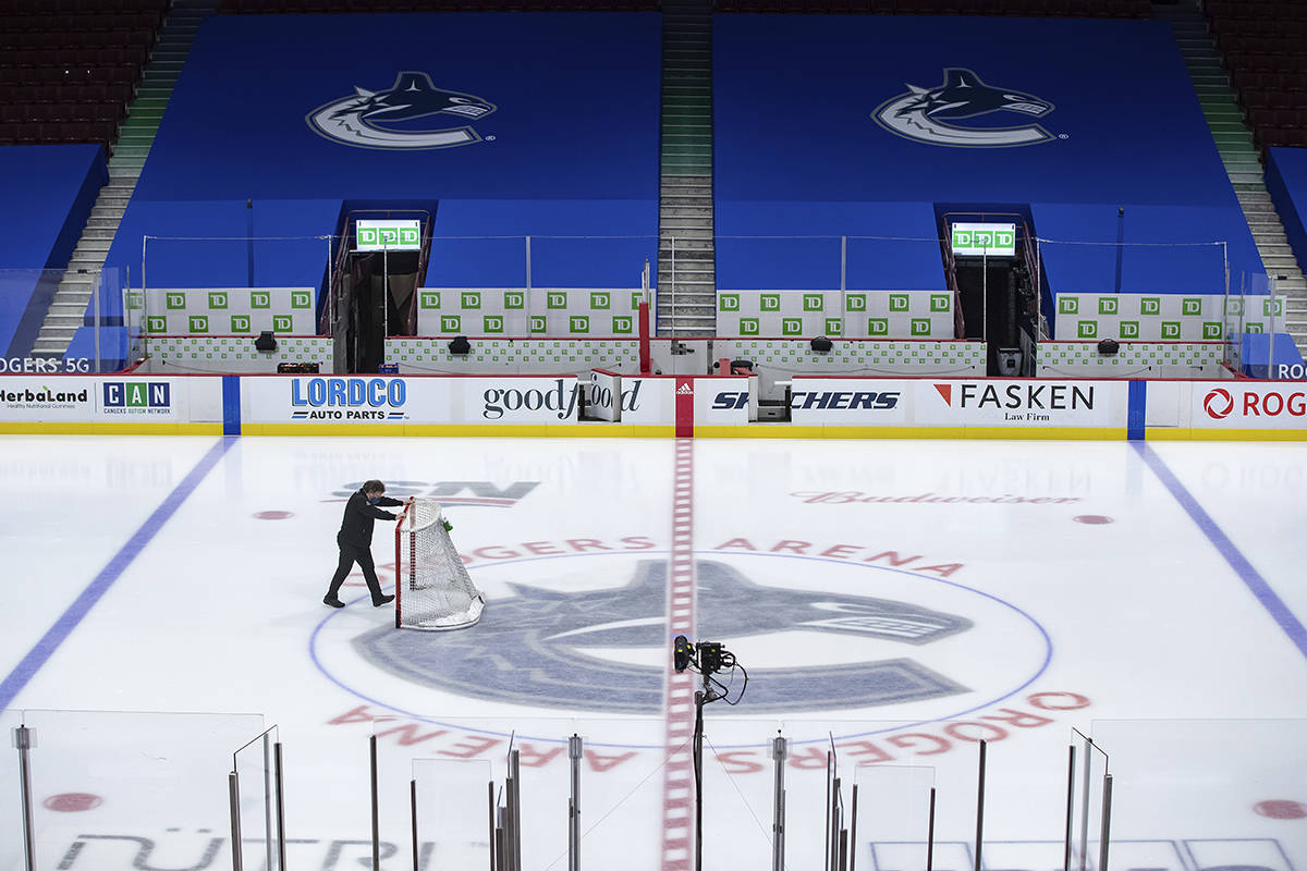 FILE - An arena worker removes the net from the ice after the Vancouver Canucks and Calgary Flames NHL hockey game was postponed due to a positive COVID-19 test result, in Vancouver, British Columbia, in this Wednesday, March 31, 2021, file photo. As vaccinations ramp up past a pace of 3 million a day in the U.S, the NHL is in a tougher spot than the other three major North American professional sports leagues because seven of 31 teams are based on Canada. (Darryl Dyck/The Canadian Press via AP, File)