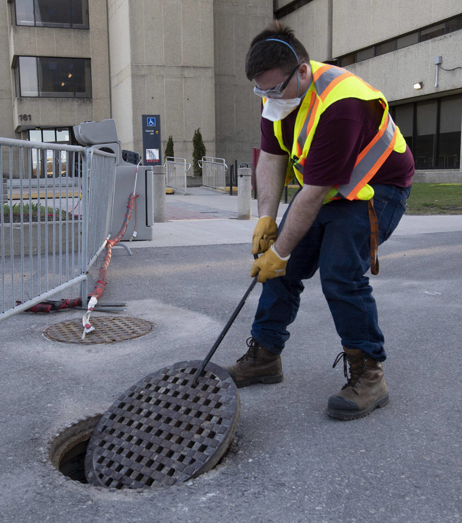 Student Patrick D'Aoust removes a manhole cover next to a wastewater collection station on the University of Ottawa campus Thursday April 8, 2021 in Ottawa. THE CANADIAN PRESS/Adrian Wyld