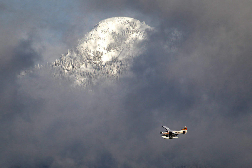 The snow-covered top of Mount Seymour is visible through low cloud as a Harbour Air floatplane approaches Vancouver, B.C., on Tuesday December 28, 2010. THE CANADIAN PRESS/Darryl Dyck