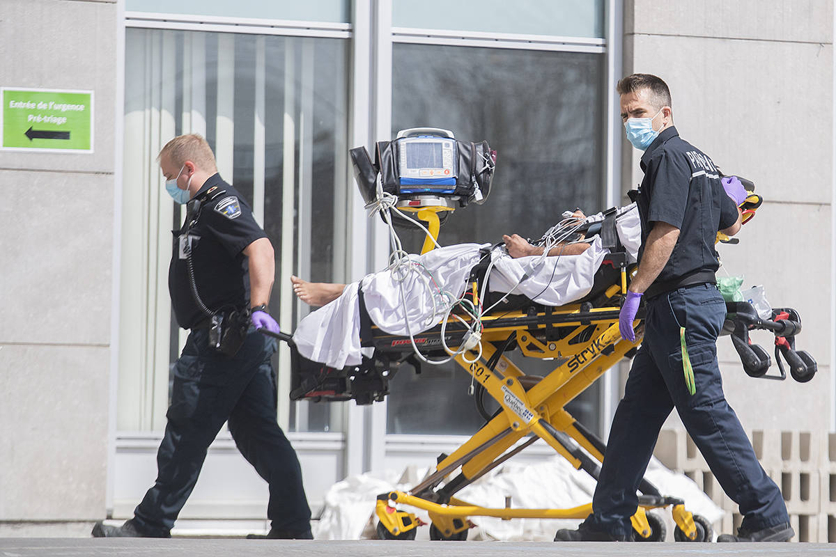 Paramedics bring a person into a hospital in Montreal, Sunday, April 11, 2021, as the COVID-19 pandemic continues in Canada and around the world. THE CANADIAN PRESS/Graham Hughes