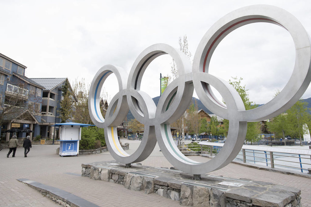 People walk past the Olympic rings in Whistler, B.C., Friday, May 15, 2020. Whistler which is a travel destination for tourists around the world is seeing the effects of travel bans due to COVID-19. THE CANADIAN PRESS/Jonathan Hayward