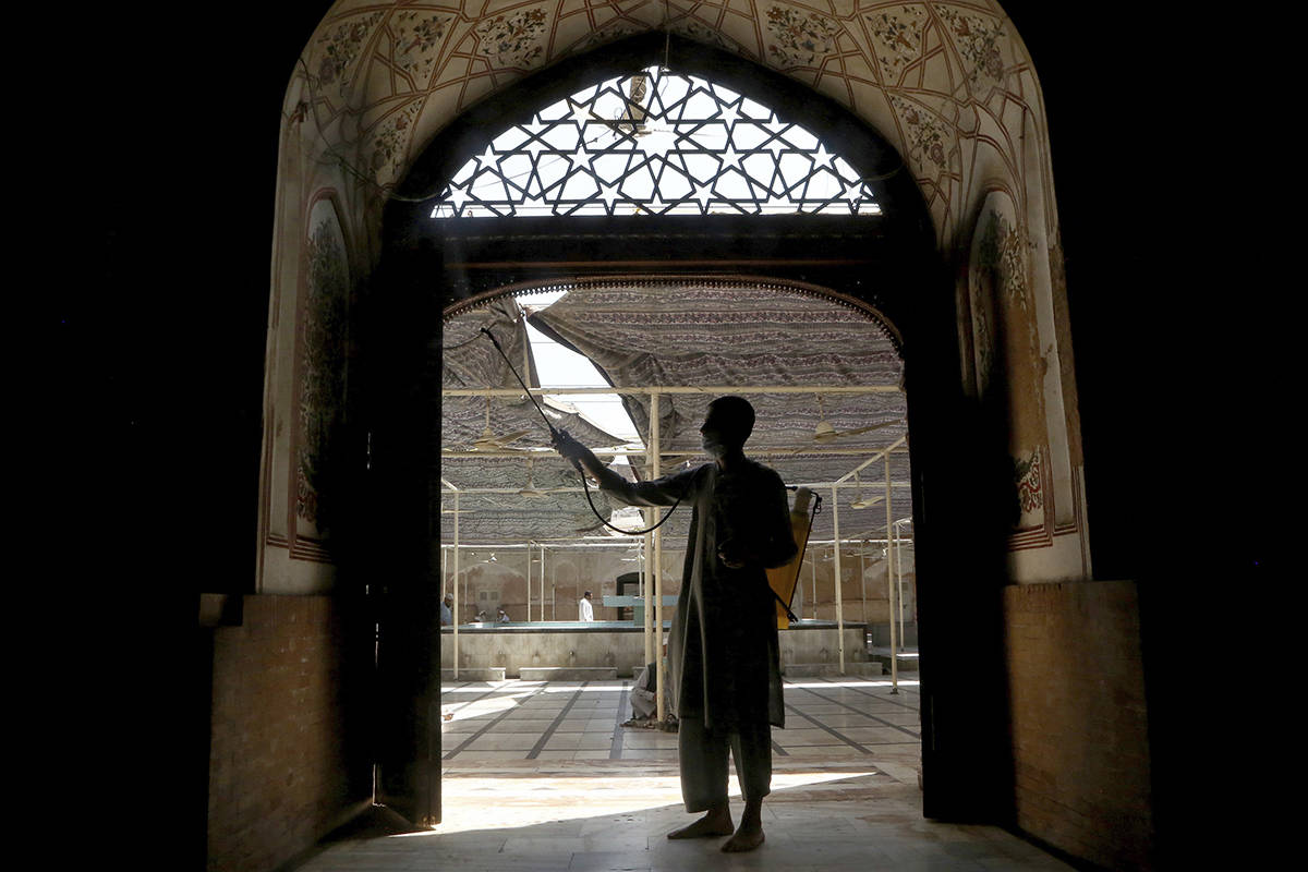 A volunteer disinfects a historical Mohabat Khan mosque ahead of the upcoming Muslim fasting month of Ramadan, in Peshawar, Pakistan, Friday, April 9, 2021. (AP Photo/Muhammad Sajjad)