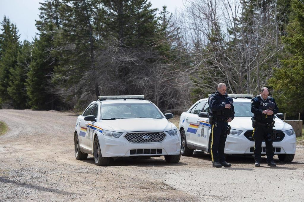 Two RCMP officers observe a moment of silence to honour slain Const. Heidi Stevenson and the other 21 victims of the mass killings at a checkpoint on Portapique Road in Portapique, N.S. on Friday, April 24, 2020. THE CANADIAN PRESS/Andrew Vaughan