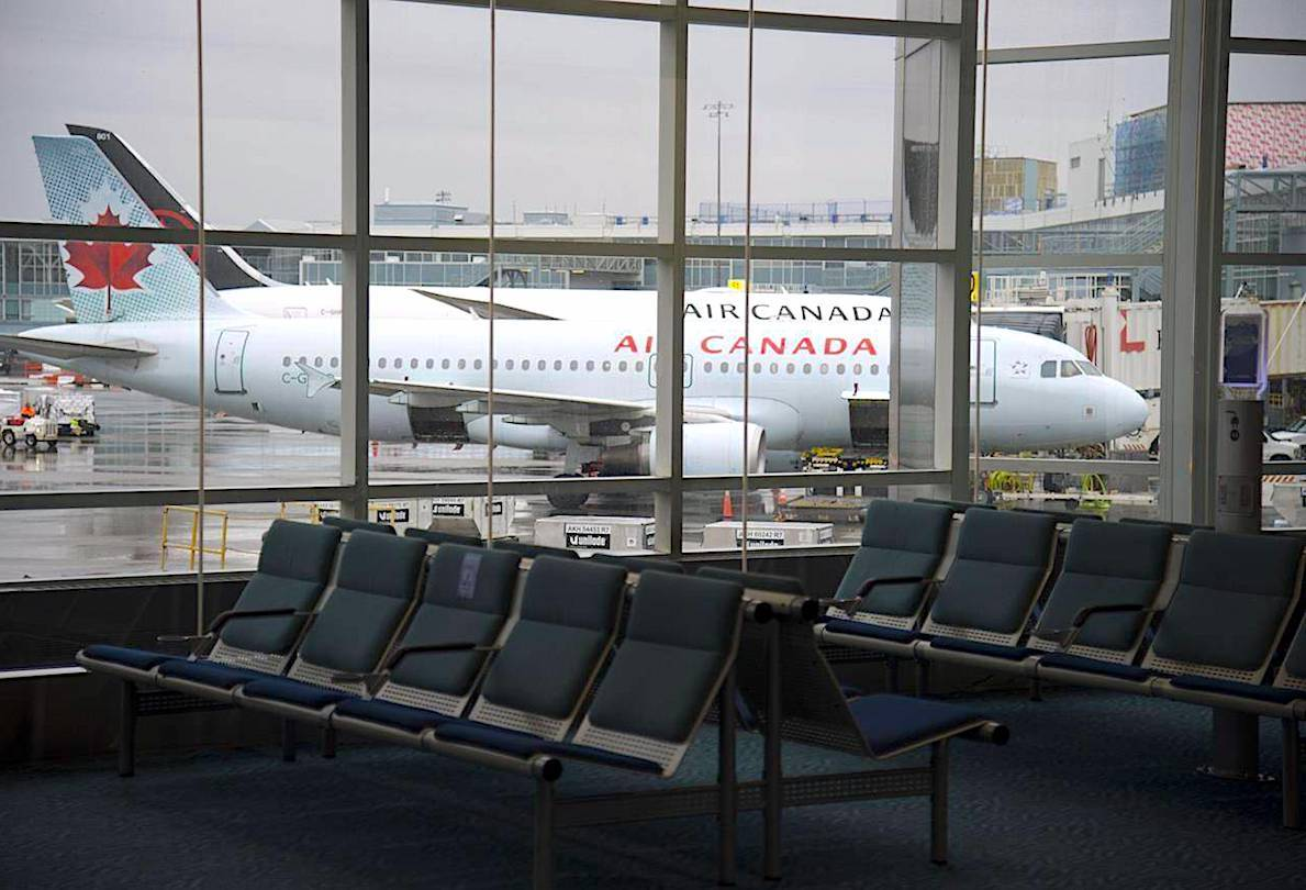 A plane is seen through the window on the tarmac of Vancouver International Airport as the waiting room is empty. THE CANADIAN PRESS/Jonathan Hayward