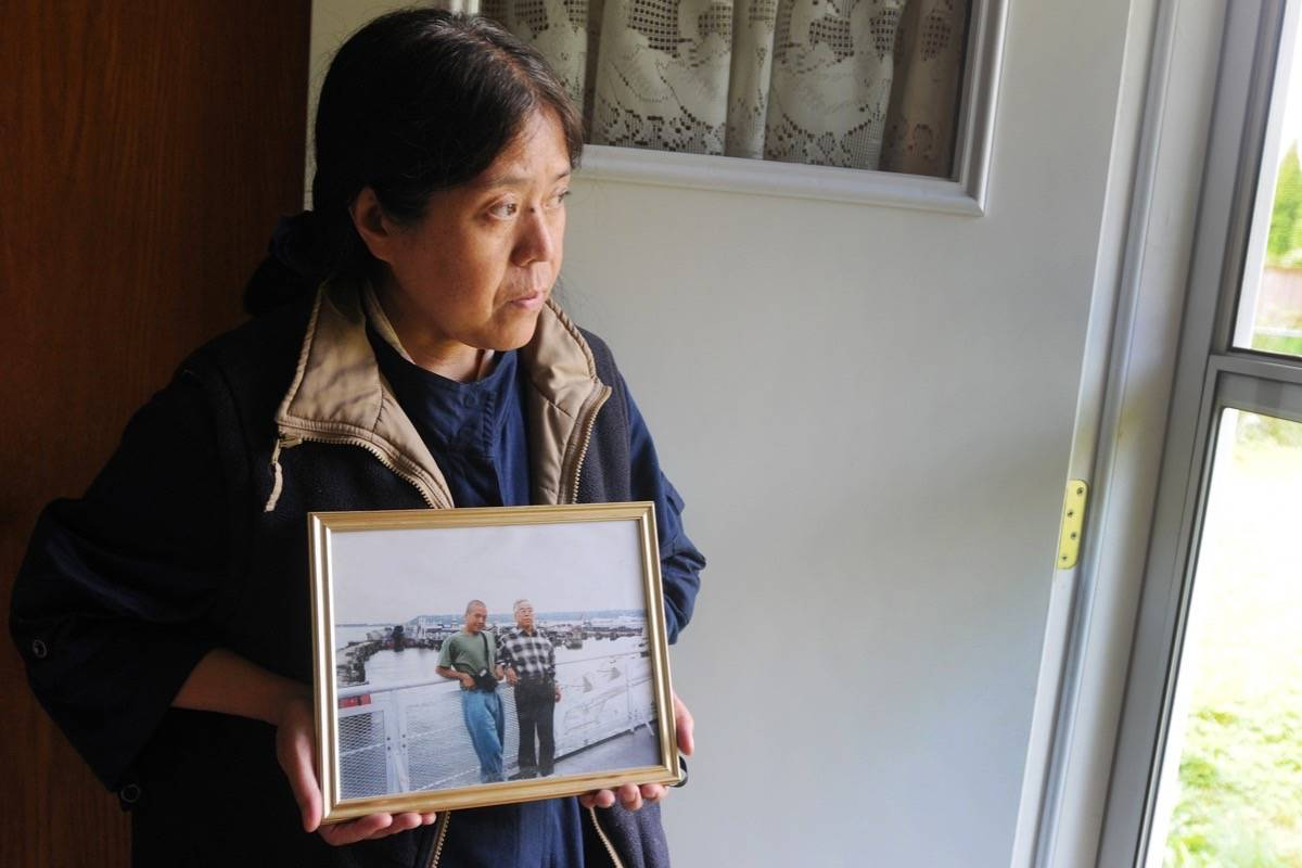 In a 2019 photograph, Yin Yin Din held a picture of her brother Kyaw Naing Din, 54, and her late father Hla Din who passed away in 2014, during a trip to Victoria. (The News files)