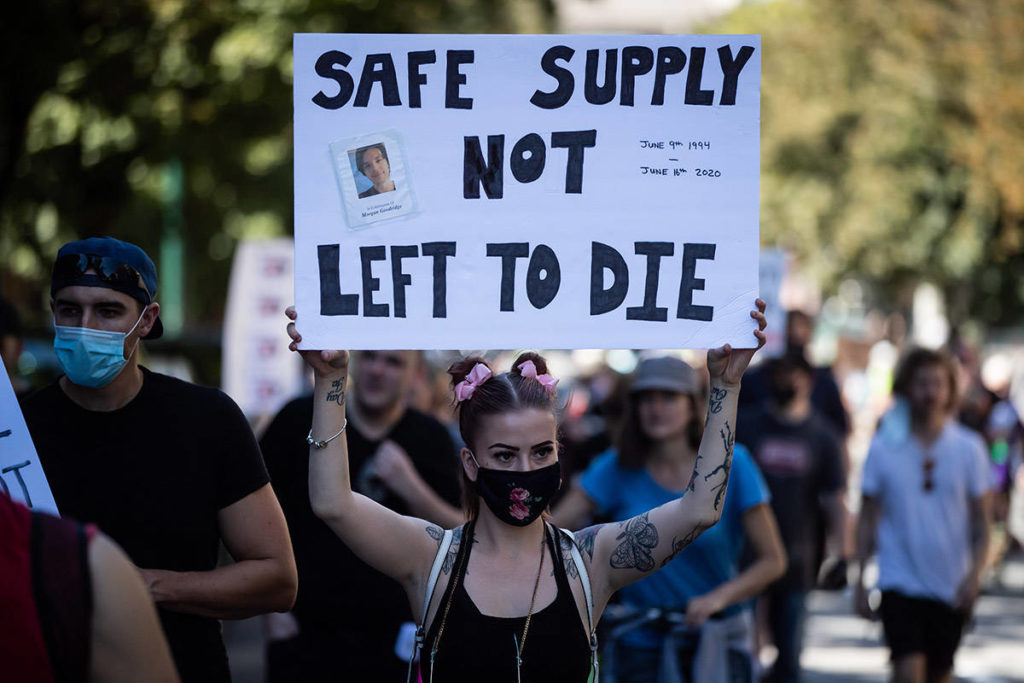 A woman holds up a sign bearing a photograph of Morgan Goodridge during a memorial march to remember victims of overdose deaths in Vancouver on Saturday, August 15, 2020. The B.C. Coroners Service reported a record number of 175 overdose deaths related to illicit drugs in June. Approximately 5,000 people have died due to illicit-drug overdoses since a public health emergency was declared in 2016. THE CANADIAN PRESS/Darryl Dyck